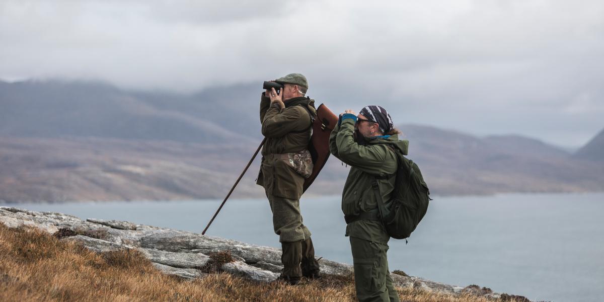 två män som spionerar efter rådjur med kustbakgrund
