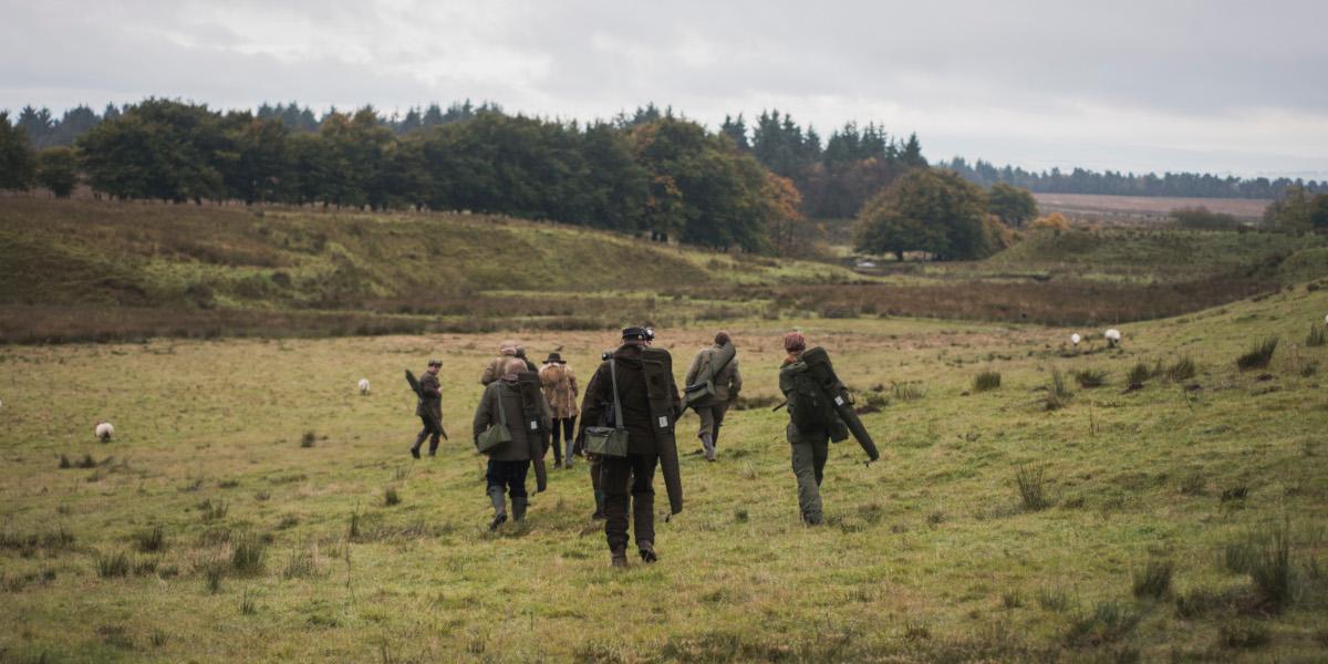 bakifrån av män med hagelgevär i fältet