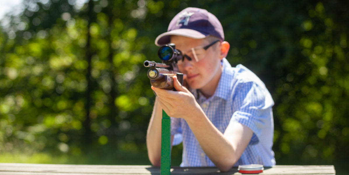 boy target shooting with air rifle and telescopic sight