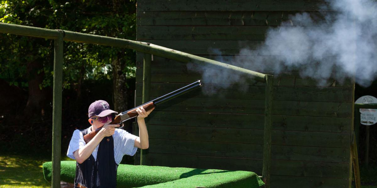 boy with shotgun firing at clay pigeon