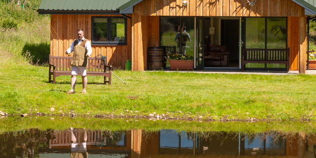 man fly fishing in front of shooting lodge