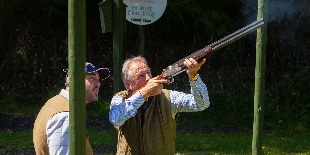 clay pigeon shooting instructor tutoring pupil