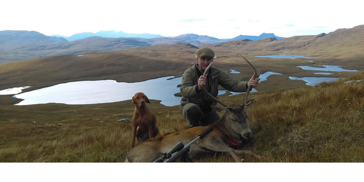 Hirschpirscher mit Rotwild Hirsch Schottland Berge mit Forellenseen dahinter