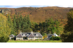 Deer stalking lodge backed by trees and mountains Scotlandking