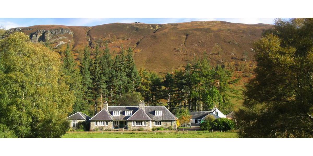 Deer Stalking Lodge hinter Bäumen und Bergen Scotlandking