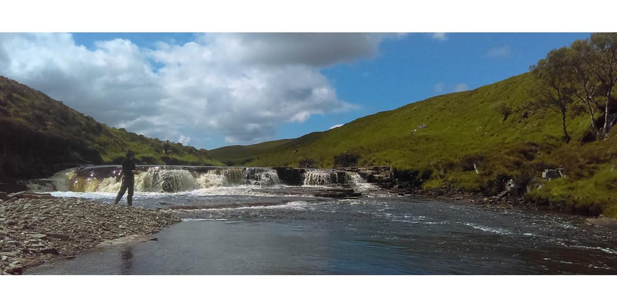 Lady angler Lachsfischen an einem Fluss in Schottland