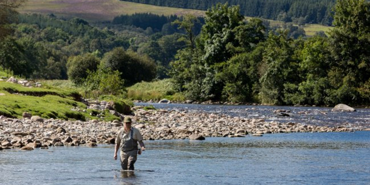 man wading a river fishing for salmon in Scotland