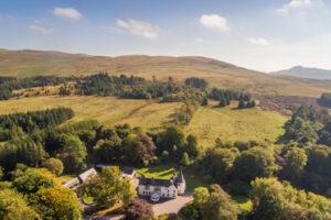 casa di campagna scozzese in un ambiente di campagna con alberi e torretta