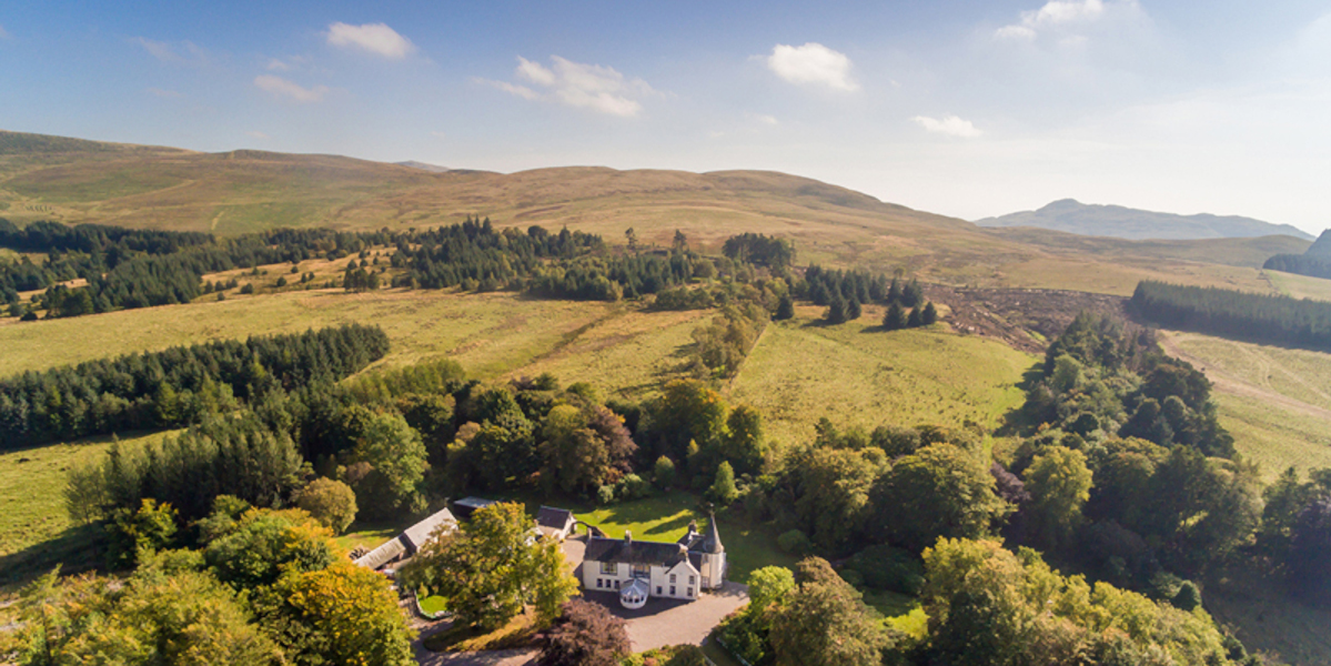 scottish country house in country setting with trees and turret