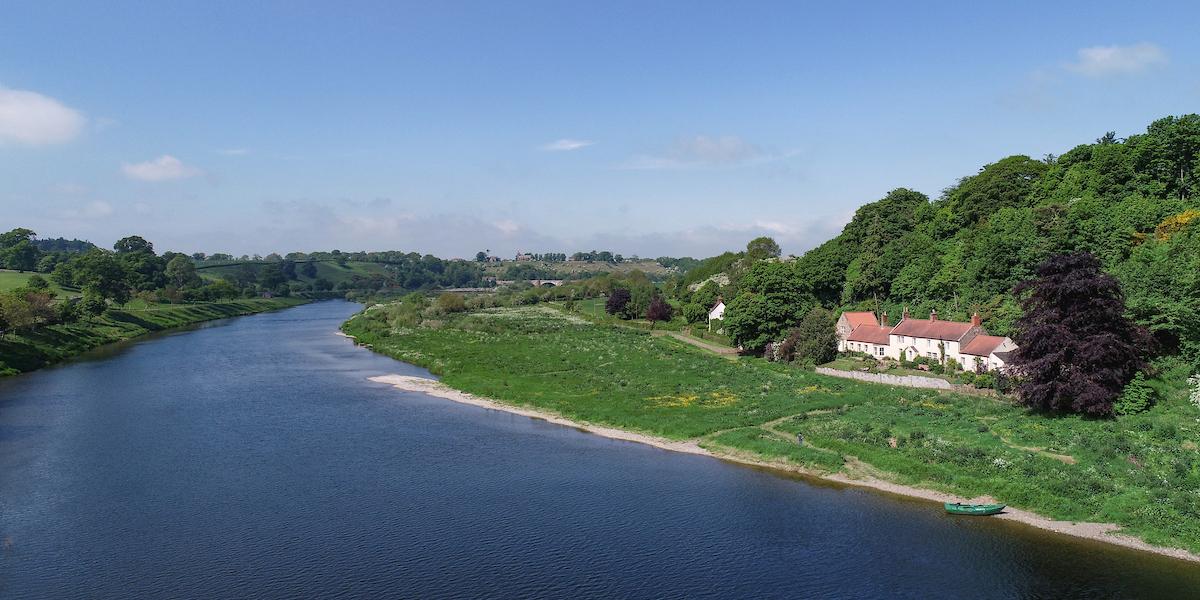 tweed de rivière avec bateau vert et maison au bord de la rivière