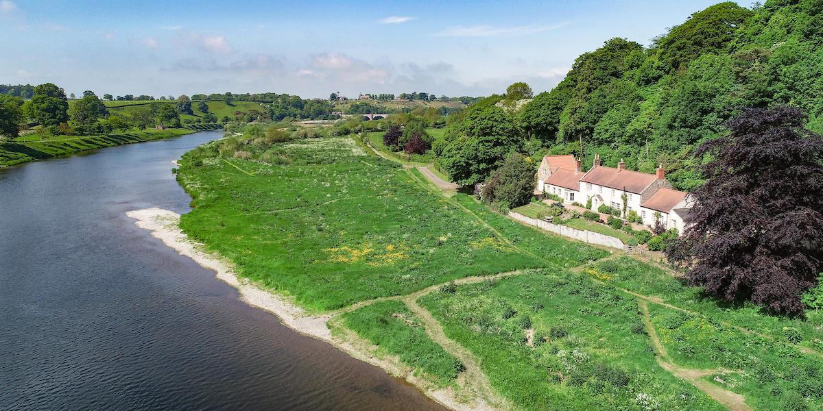 River Tweed avec bateau vert et maison au bord de la rivière