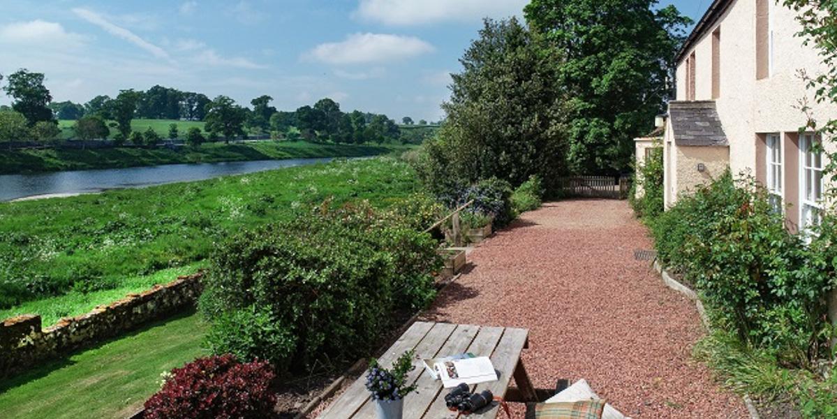 Table de pique-nique sur chemin de gravier avec des jumelles à côté d'une rivière