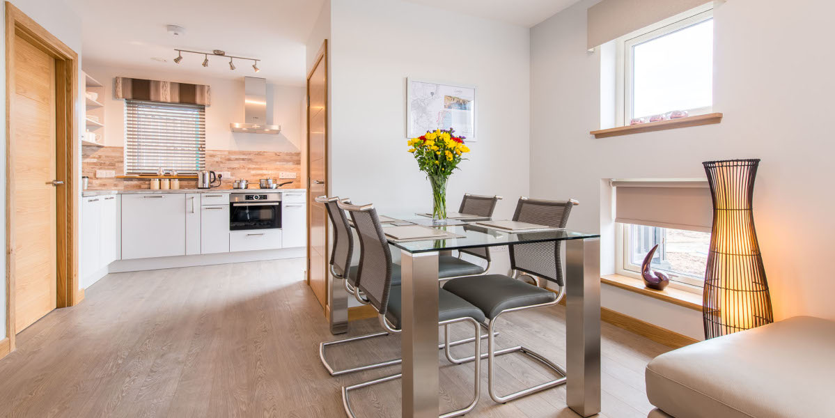 glass dining table with 4 chairs and kitchen beyond