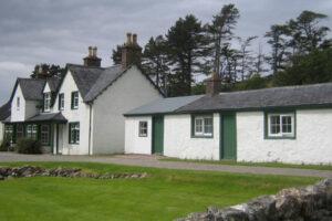 Rifugio_di_caccia_scozzese_nelle_highlands_dipinto_di_bianco_con_porte_dipinte_di_verde_e_finestre_luci
