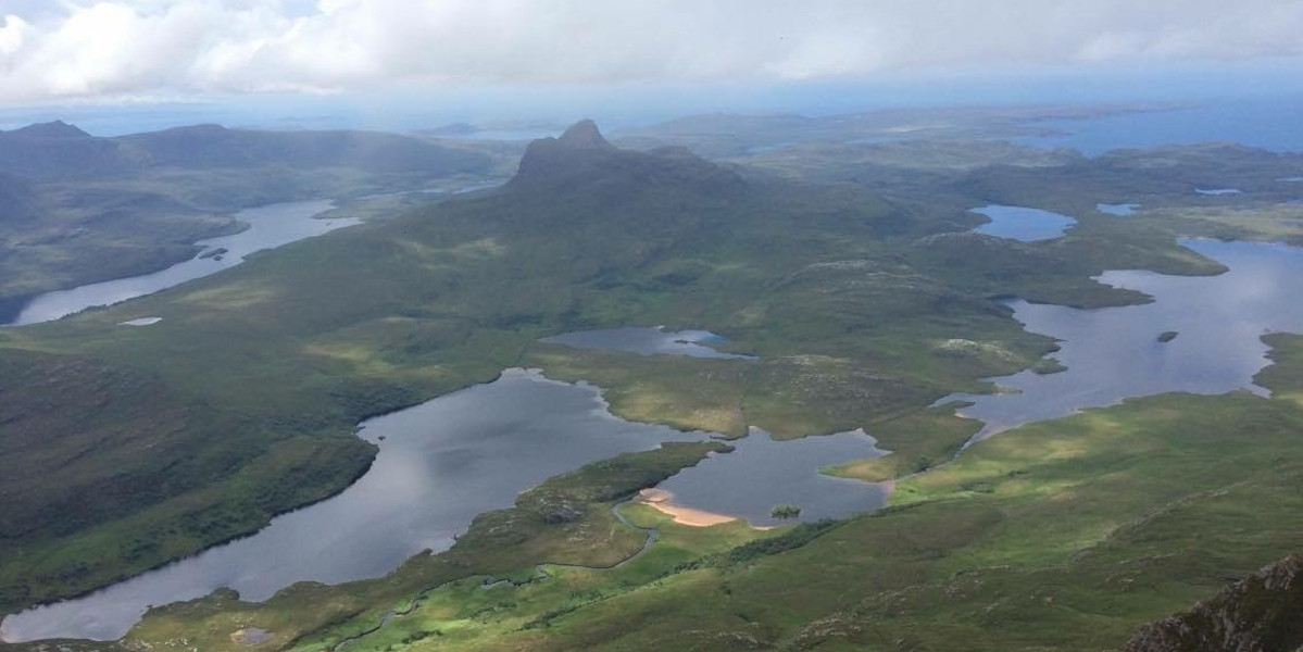 Scottish_highlands_looking_down_on_scene_of_mountains_and_lochs