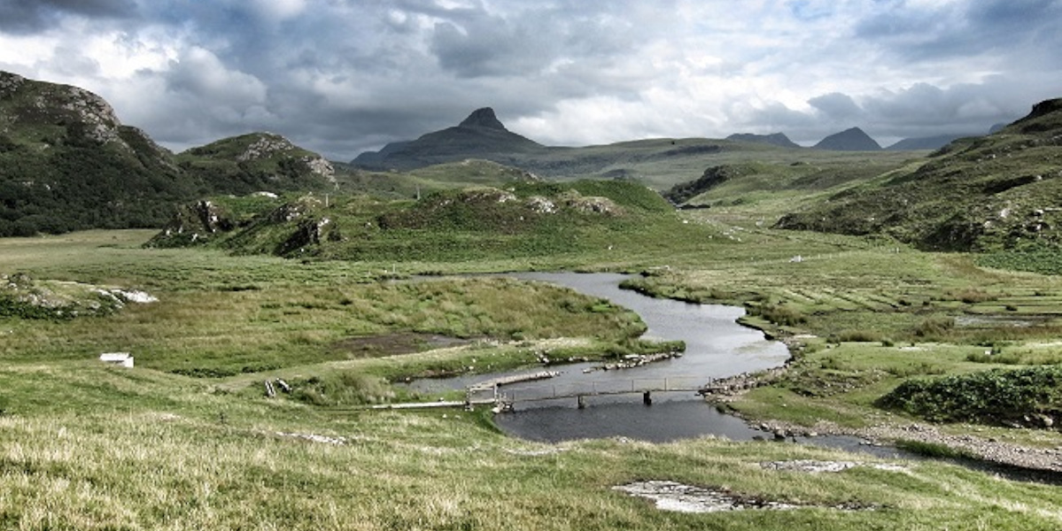 Scottish_highland_scene_with_mountains_ and_river_with_wooden_bridge_crossing