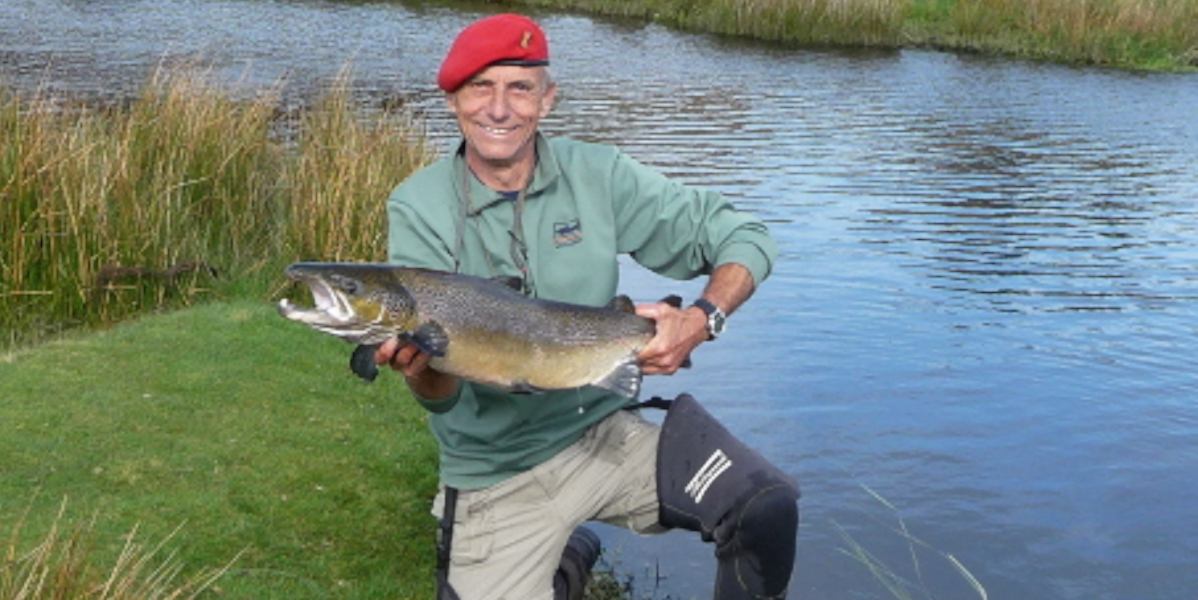Scottish_salmon_fisherman_wearing_red_beret_ and_waders_holding_salmon_beside_river