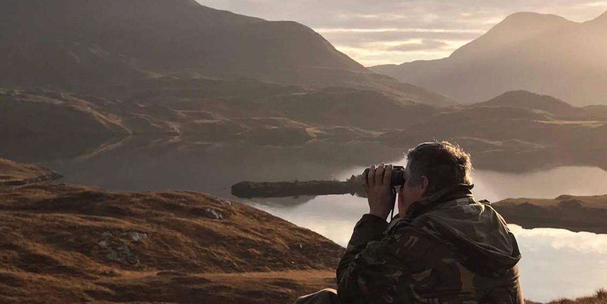 Stalker_in_Scottish_highlands_beside_loch_spotting_red_deer