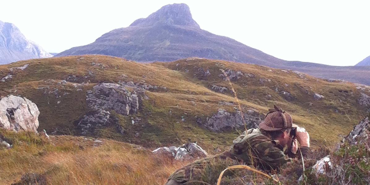 Scottish_deer_stalker_lying_in_grass_amidst_mountains_wearing_camouflage_jacket_spotting_red_deer