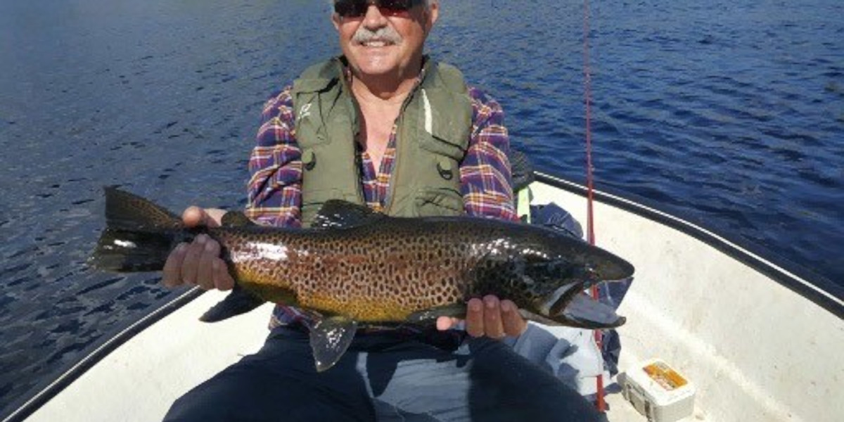 fisherman_in_boat_with large_wild_Scottish_brown_forelle