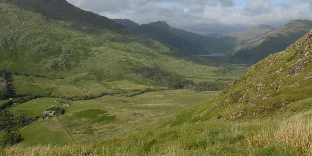 Sikt från det skotska berget med utsikt över Glen med bondgårdfloden och loch