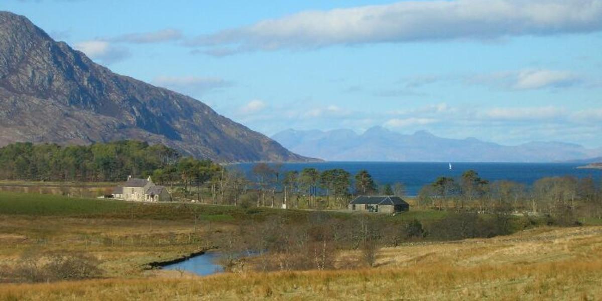 Skotsk höglandslantgård och ladugård med utsikt över havet med berg i bakgrunden