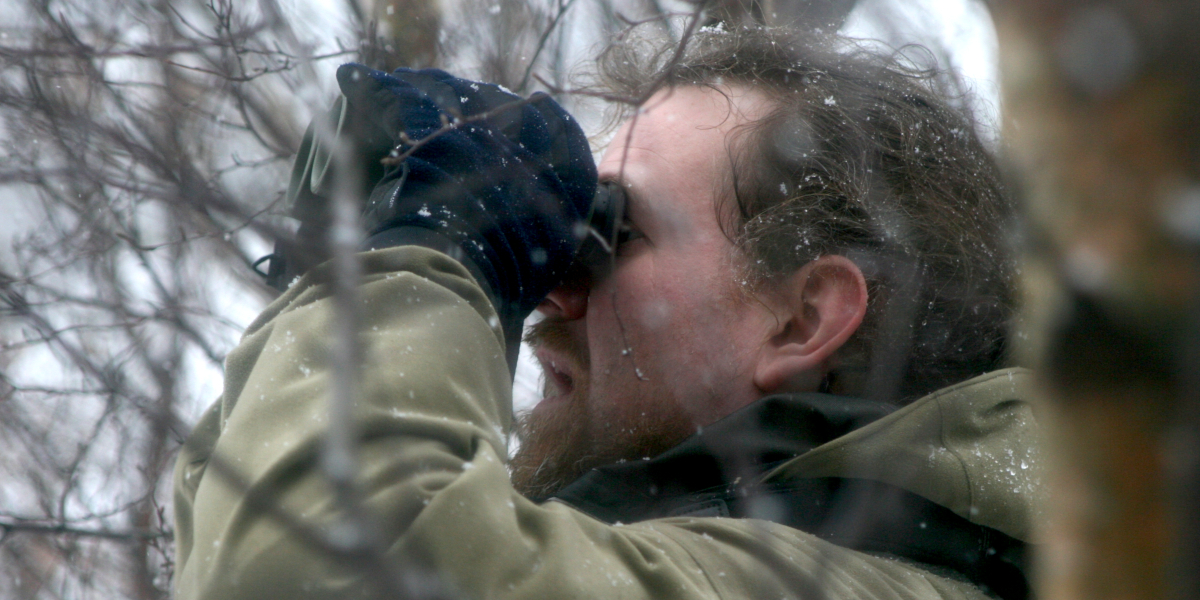 man använder kikare i snö