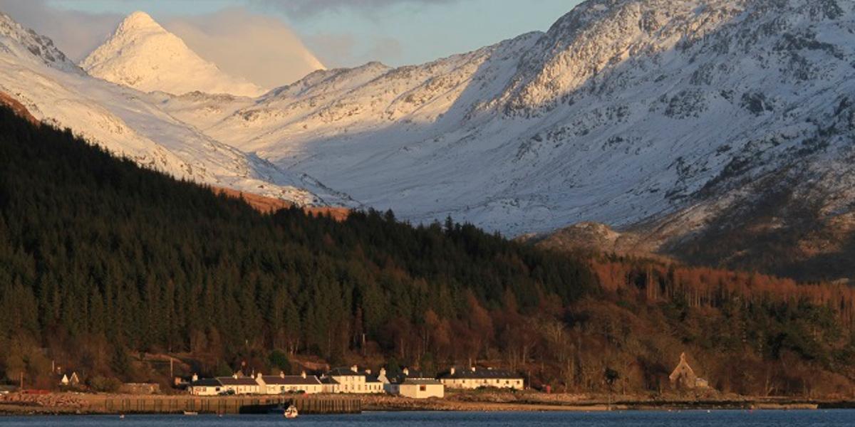 Skotsk höglandsby på stranden med träd och snöklädda berg bakom