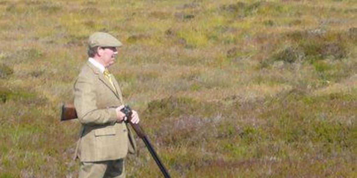 man i tweed med hagelgevär på grouse hed