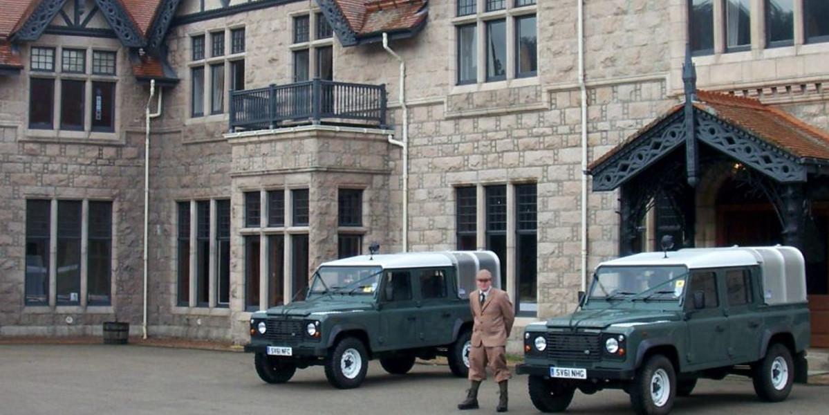 Scottish Estate Game Keeper utanför lodge med 2 Land Rover försvarare