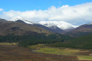 Scottish estate view valley wooded hillside and snowy mountain tops