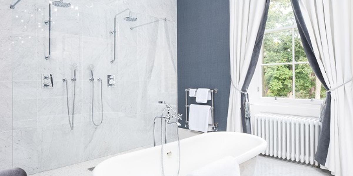 salle de bain d'hôtel de luxe baignoire et douches jumelles