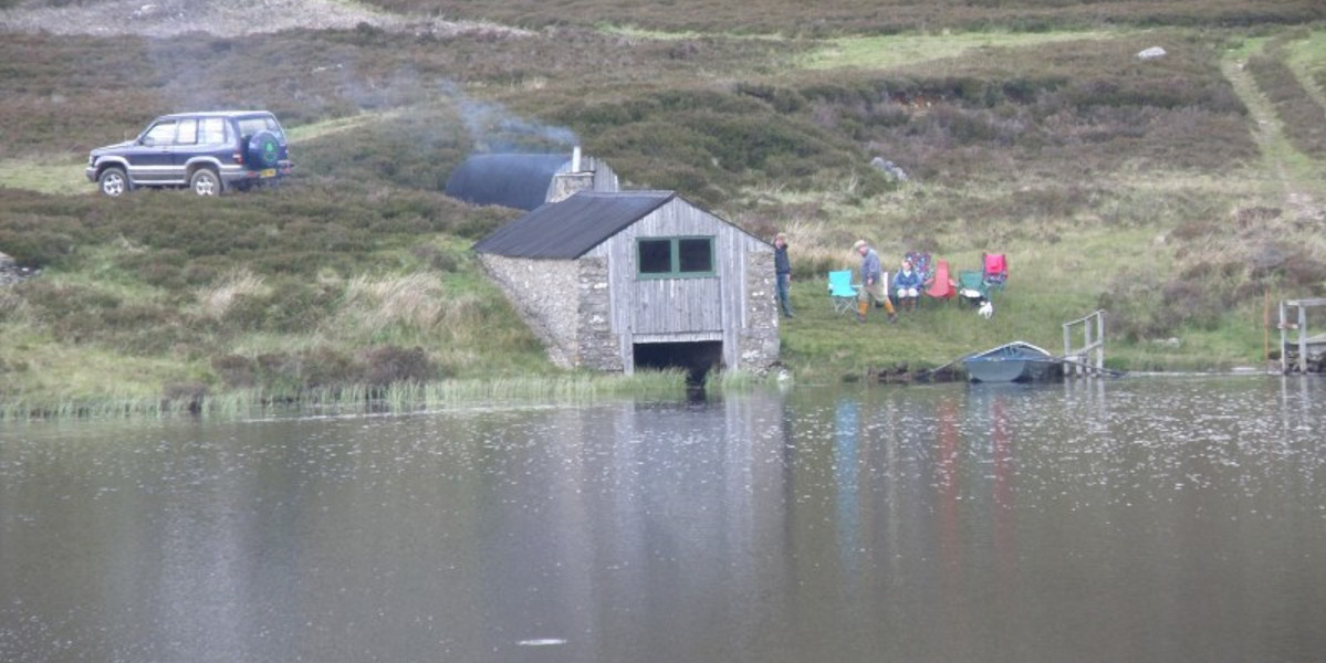 Bootshaus und Angler am schottischen Hügelloch