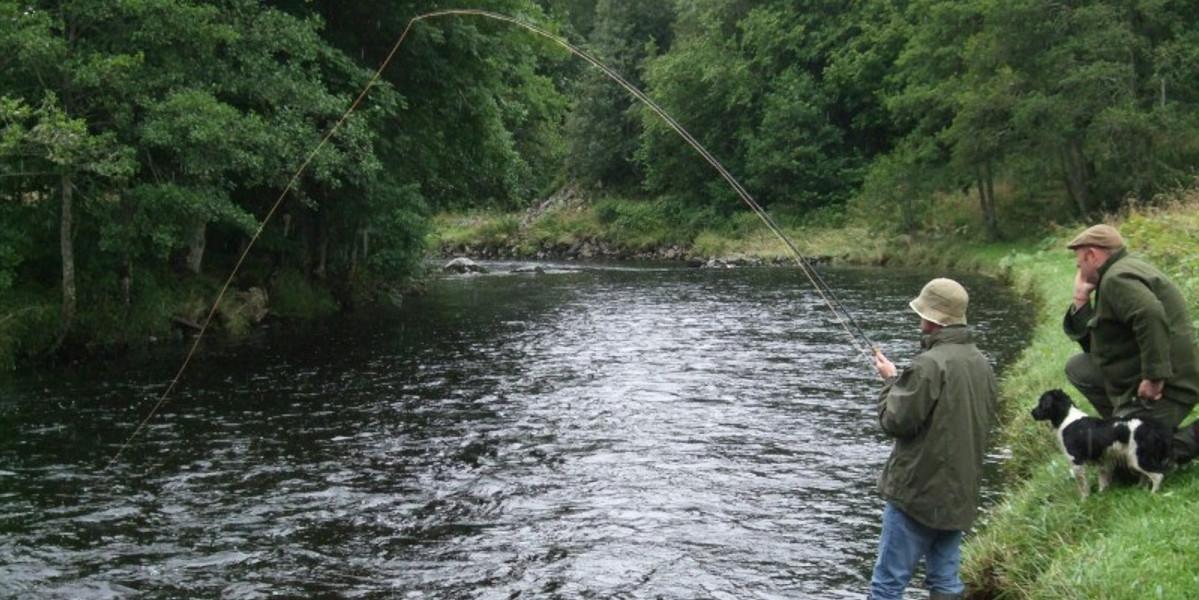 Angler und Ghillie spielen einen Fisch im Fluss