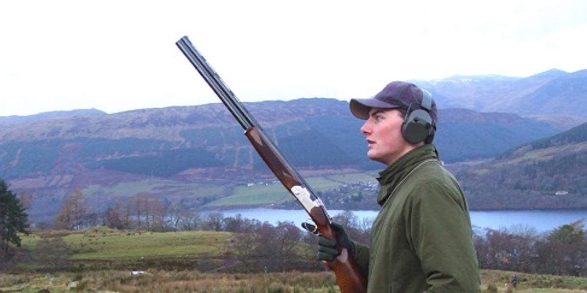 junge Waffe in Tweed mit Ohrenschützern über dem schottischen Loch