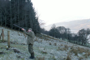pheasant shooter on frosty hillside with fir trees in background