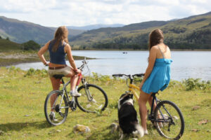two girls on bicycles overlooking Scottish highland loch