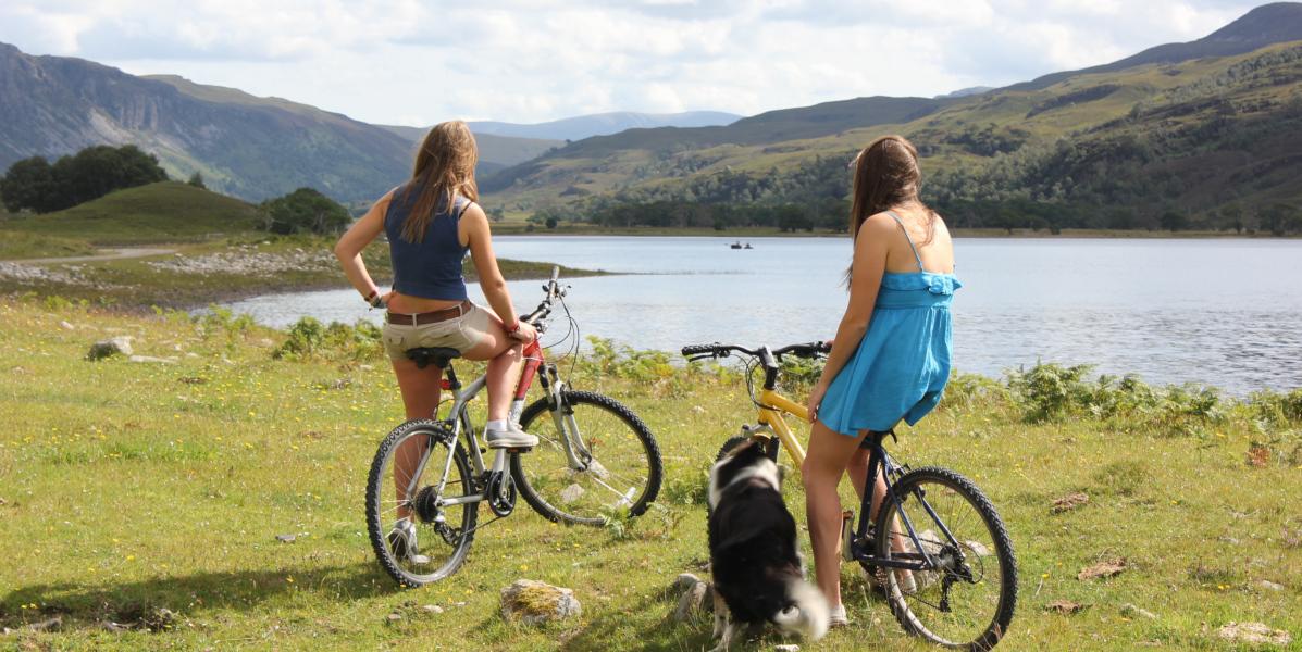zwei Mädchen auf Fahrrädern mit Blick auf das schottische Hochlandloch