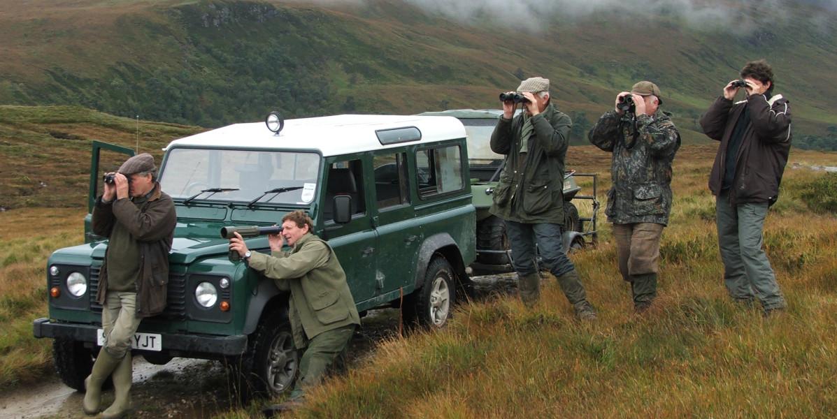 fünf Stalker neben grünem Land Rover Defender, der Rehe ausspioniert