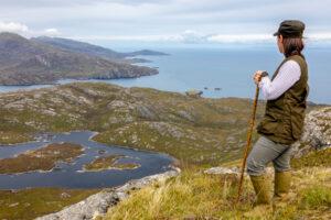 Scottish island woman on hill overlooking sea