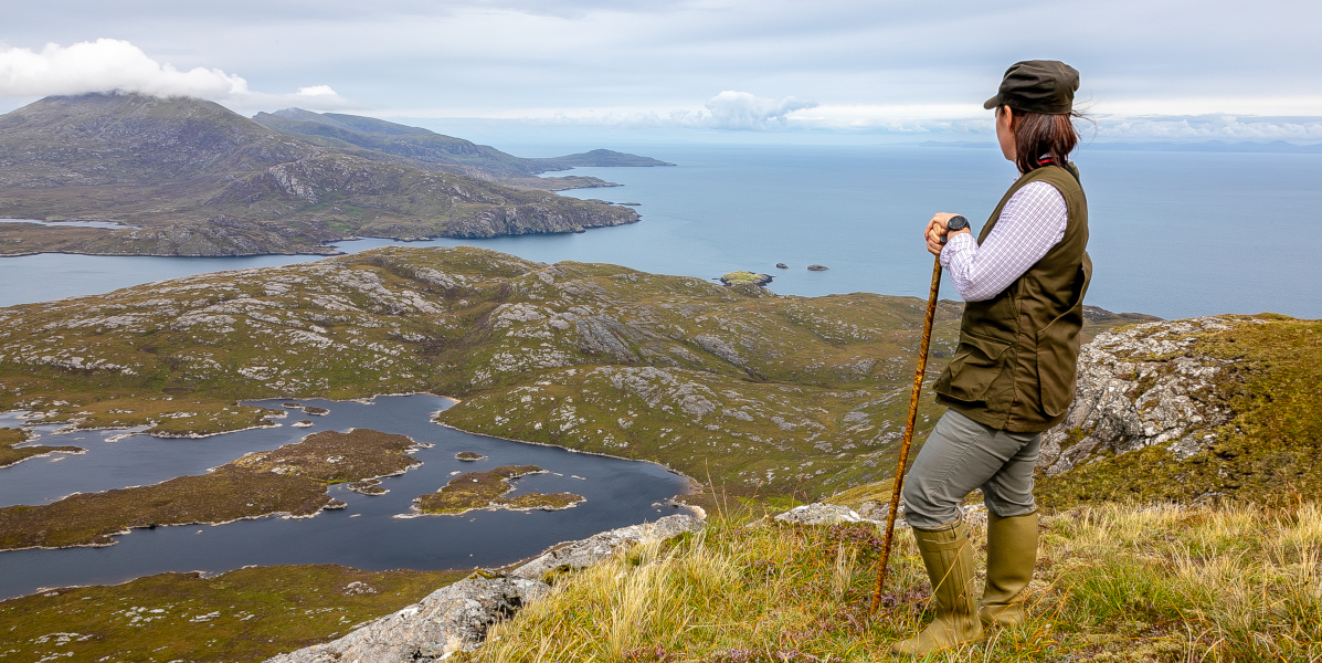 Schottische Inselfrau auf Hügel mit Blick auf Meer