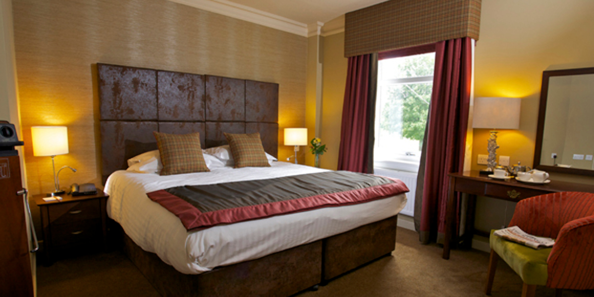 contemporary hotel bedroom white linen and brown scatter cushions