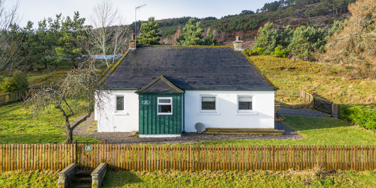 white washed Scottish cottage with green porch