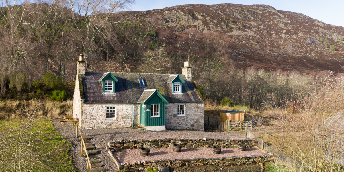 two storey Scottish stone built cottage with green woodwork