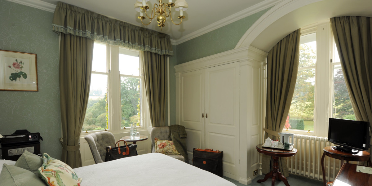 hotel double bed room with green decorv and double aspect windows