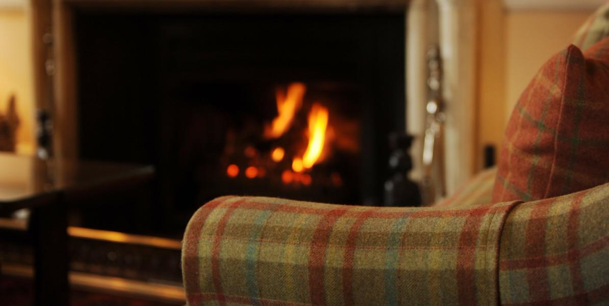 tartan fireside chair with lit open fire