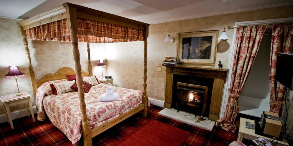 hotel room with lit open fire and 4 poster bed