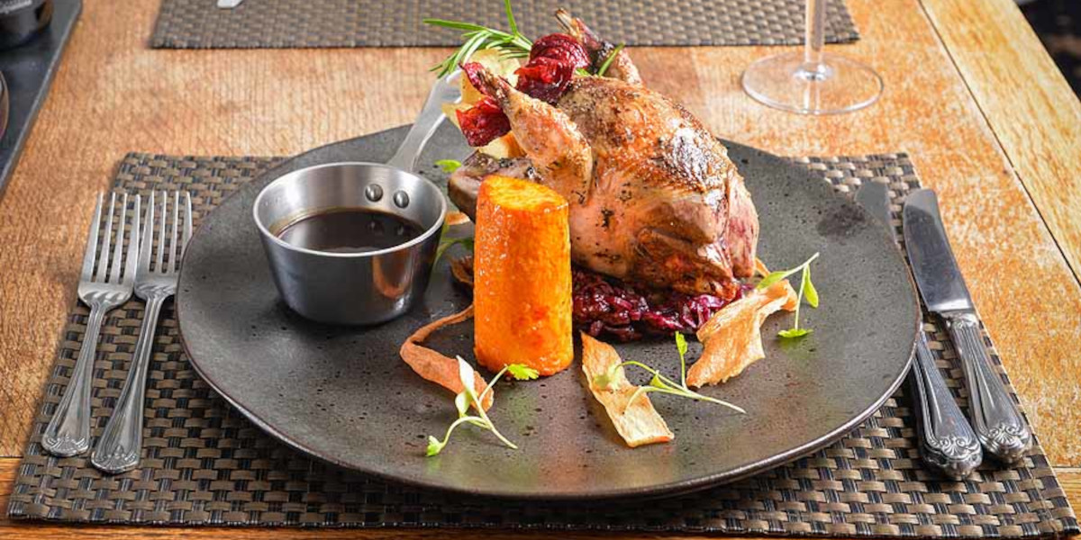 hotel plate of food grouse with vegetables and gravy pourer