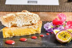 piatto dell'hotel di torta meringata al limone di cibo dolce e frutto della passione