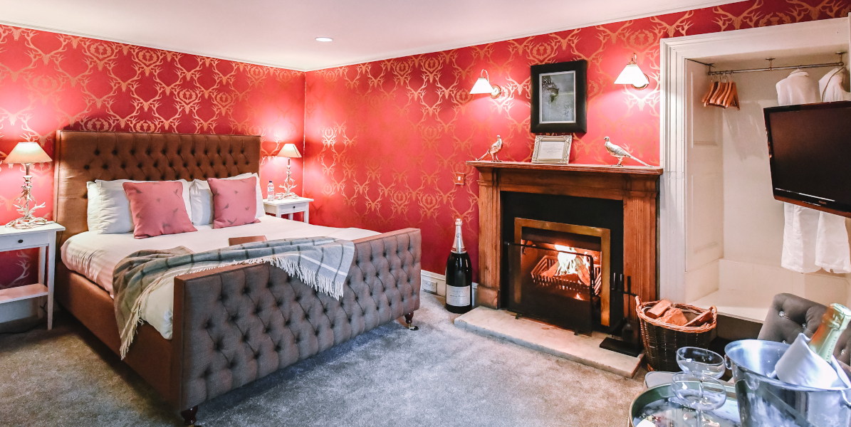 Hotel bedroom with open fire and red wallpaper